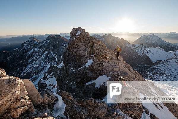 Two mountaineers climbing on mountain peak in European Alps