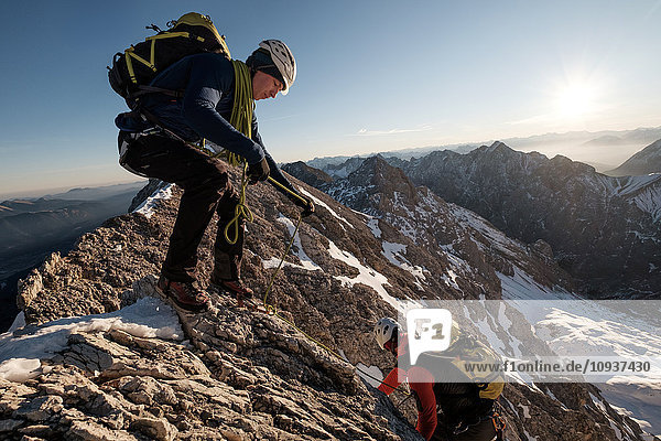Two mountaineers climbing mountain peak in European Alps