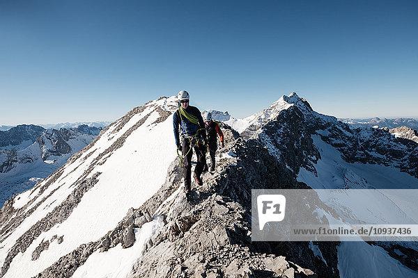Two mountaineers hiking on mountain peak in European Alps