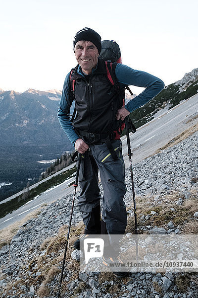 Mountain guide with backpack and hiking poles in European Alps