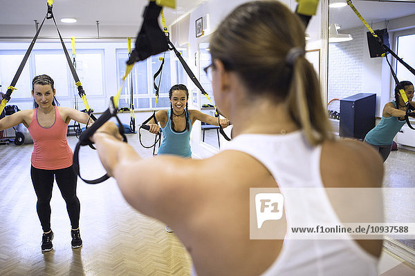 Women in exercise class doing suspension training