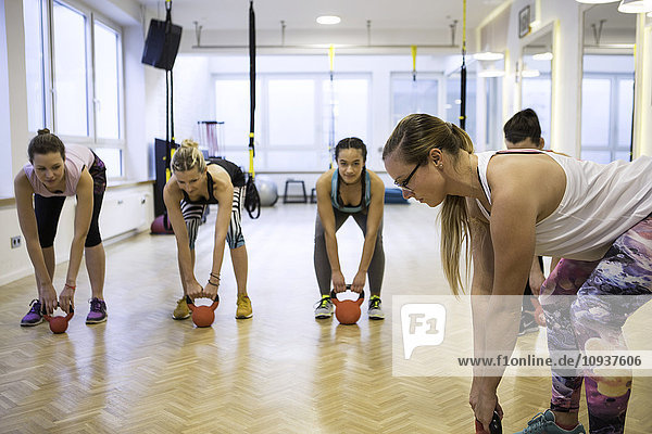 Women in exercise class practicing with kettlebells