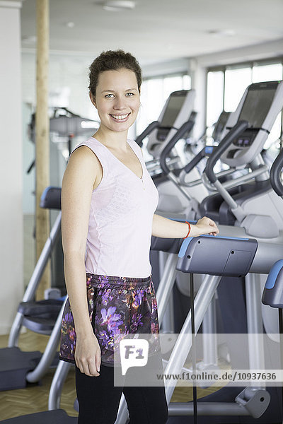 Beautiful woman in health club with exercise equipment in background