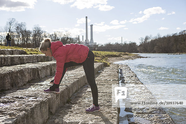 Blond woman tying sports shoe lace by the riverside