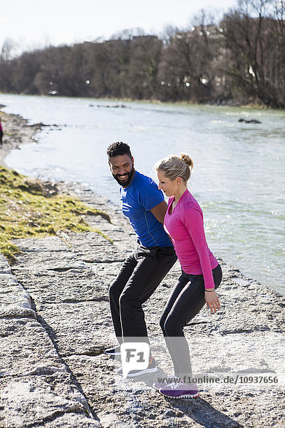 Young couple exercising by the riverside