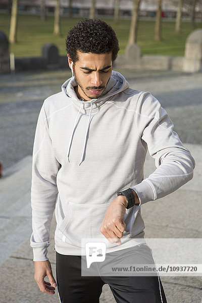 Man in sports clothing checking smart watch