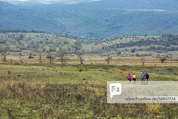 Group of friends mountain biking in hilly landscape