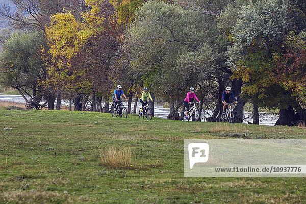 Group of friends mountain biking in meadow