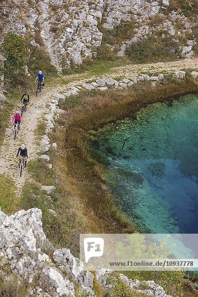 Group of friends mountain biking on trail next to lake