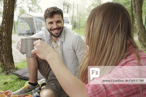 Young couple drinking coffee at campsite