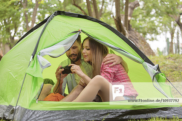 Young couple in tent looking at camera