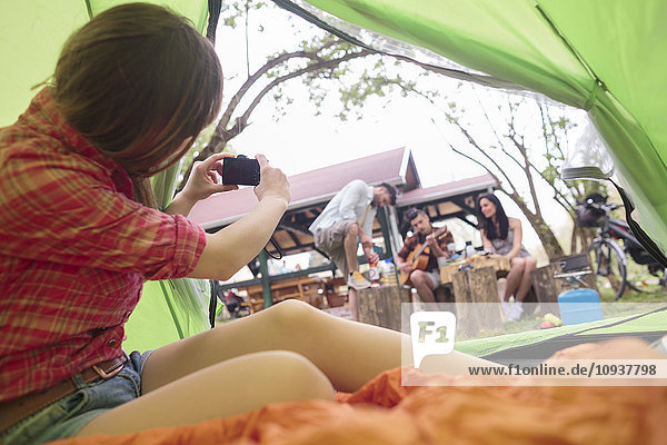 Young woman photographing friends at campsite