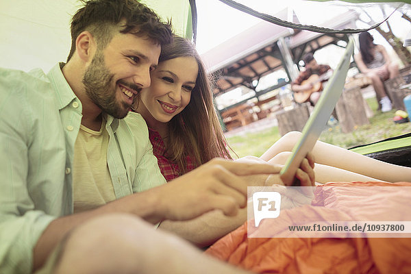Young couple at campsite using digital tablet