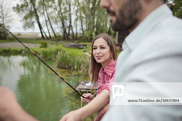 Young couple fishing together in lake