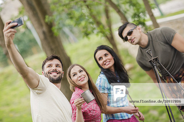 Group of friends taking selfies at campsite
