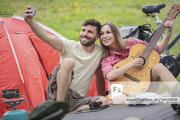 Young couple at campsite taking selfie