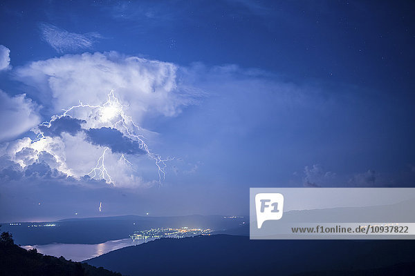 Lightnings in thunderstorm over coastline at night