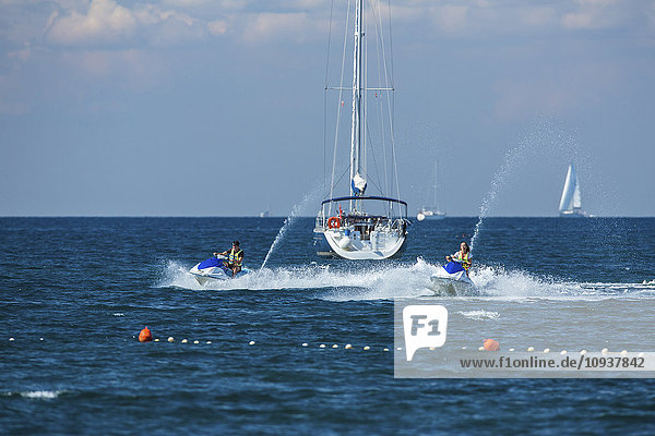 Jet boats racing at high speed next to sailboat