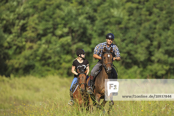 Couple horseback riding in field