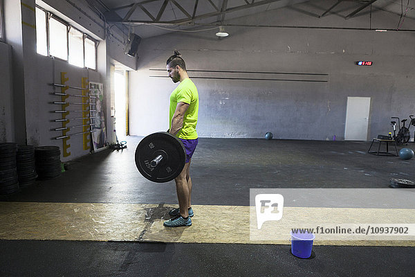 Athlete lifting a barbell in gym