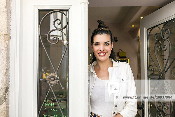 Portrait of young woman in door of restaurant