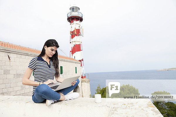 Young woman using laptop with lighthouse in background
