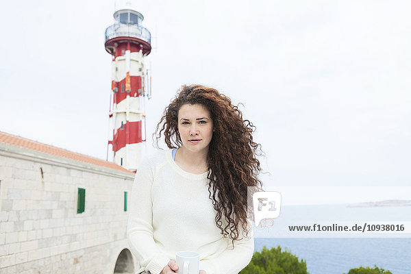 Young woman takes a break with lighthouse in background