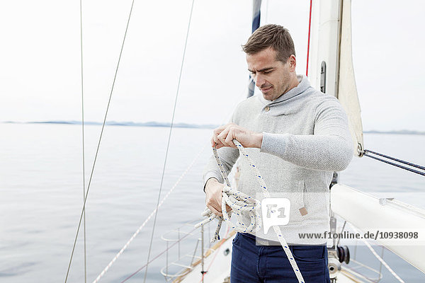 Man on yacht curling up rope