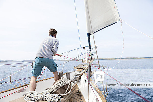 Man pulling on rope on yacht