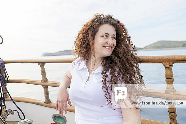 Portrait of beautiful woman with curly hair on sailboat