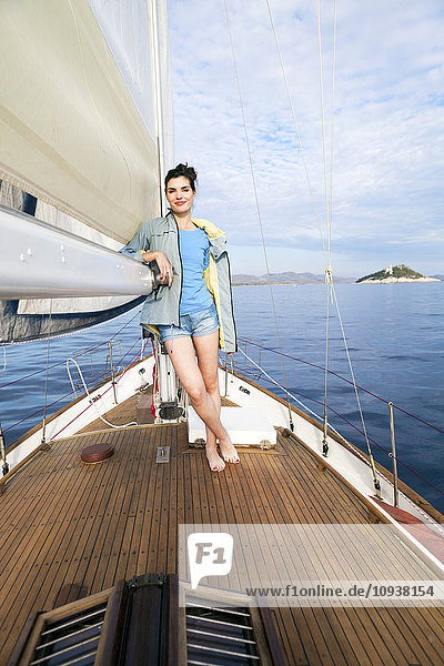 Young woman leaning on sailboat sail