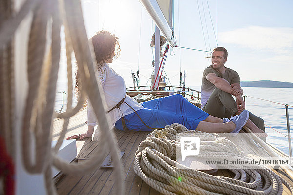 Young couple on sailboat relaxing