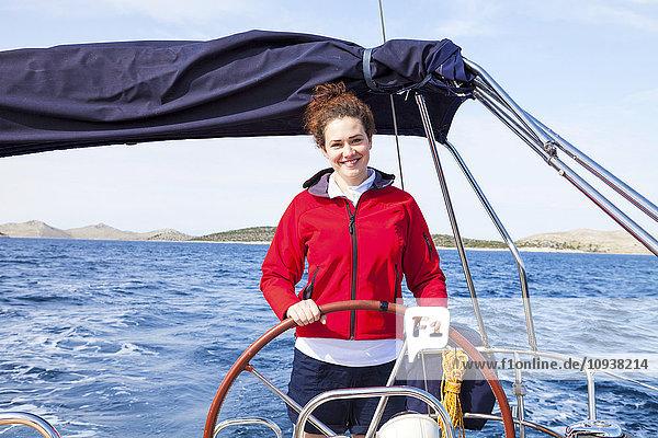 Woman at steering wheel of sail ship