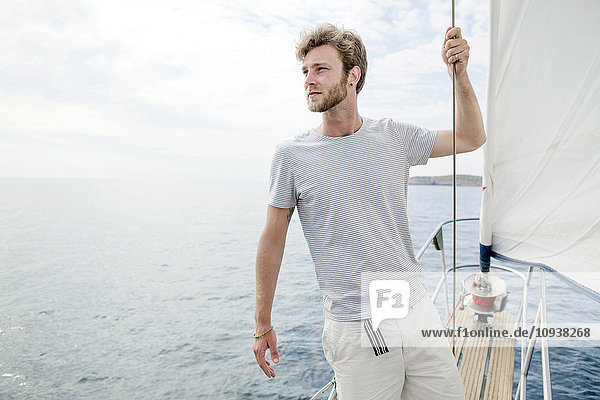 Man on sailboat looking out over sea