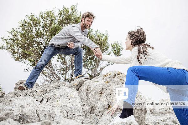 Man helping woman climb rock formation