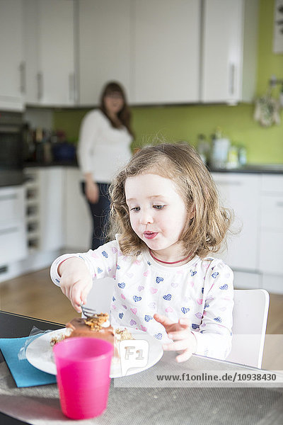 Toddler girl eating cake with mother in background