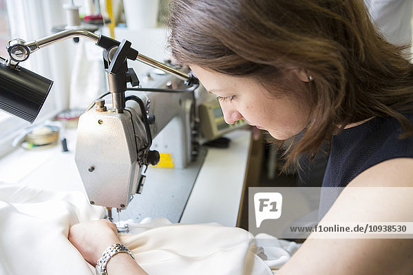 Woman working at sewing machine in bridal shop