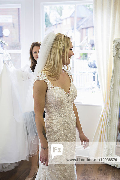 Female customer in bridal shop trying on wedding dress