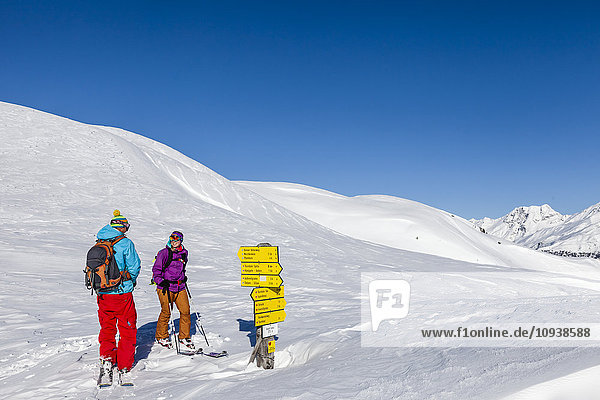 Skitourers looking at signpost in Alpine landscape