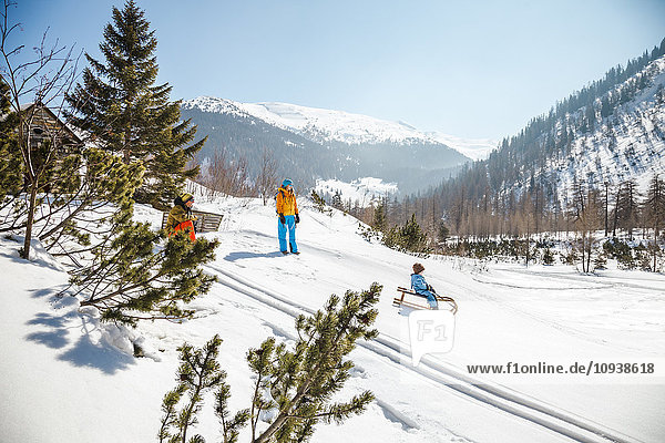 Boy sledding downhill with parents watching