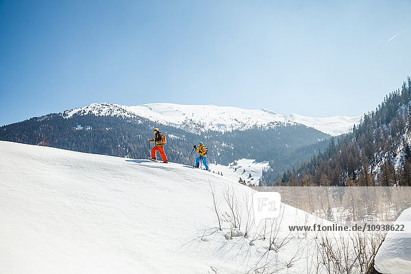 Two people snowshoeing in Alpine scenery