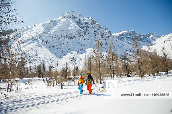 Family pulling sledge with son in Alpine winter scenery