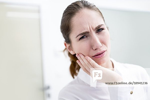 Young woman suffering toothache