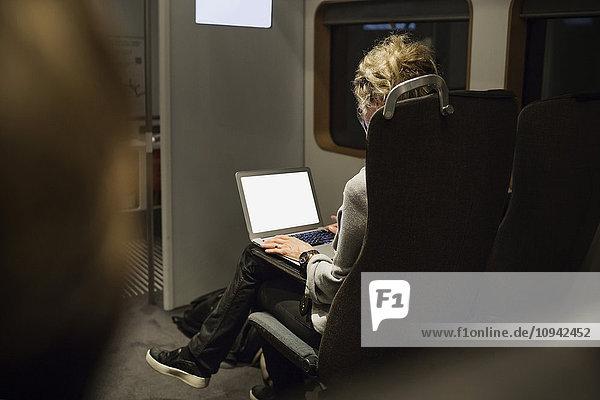 Rückansicht der Geschäftsfrau mit Laptop im Zug
