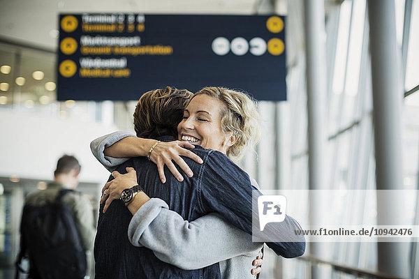 Glückliche Geschäftsfrau umarmt männlichen Kollegen am Flughafen Glückliche Geschäftsfrau umarmt männlichen Kollegen am Flughafen