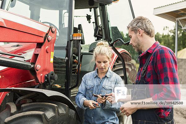Mann und Frau halten Ausrüstung  während sie auf dem Bauernhof neben dem Traktor stehen.