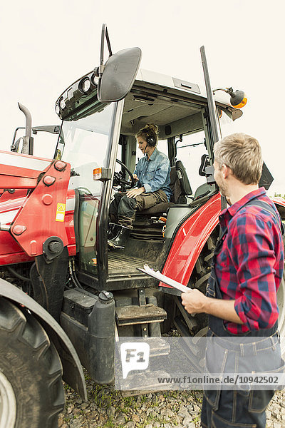 Mann schaut auf Traktorfahrerin in der Landwirtschaft