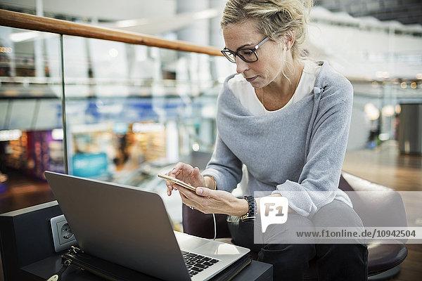 Geschäftsfrau mit Smartphone und Laptop in der Flughafenlobby
