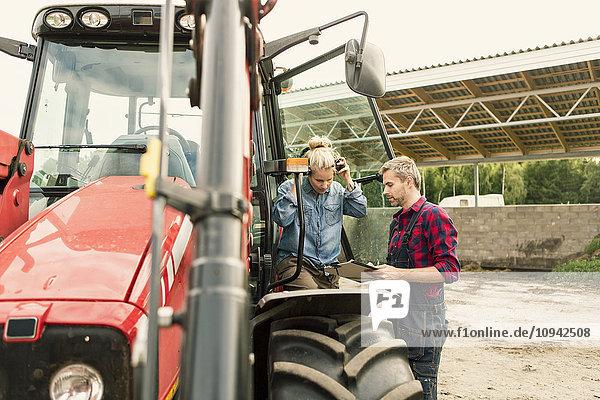 Paar bespricht Dokument mit dem Traktor auf dem Bauernhof