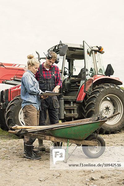 Frau und Mann diskutieren mit dem Traktor über ein Dokument auf dem Bauernhof.